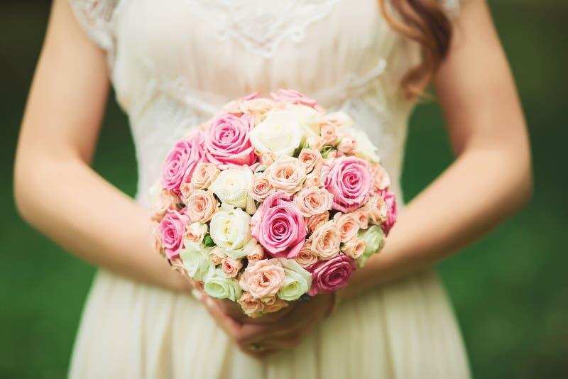 Ramo hermoso de la boda en las manos de la novia imagenes de archivo