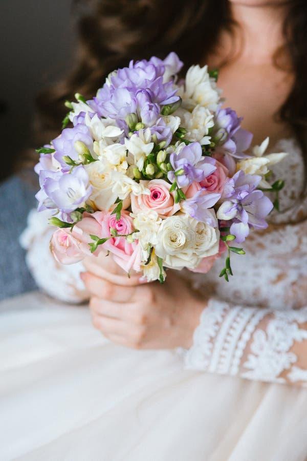 Ramo hermoso de la boda en las manos del ` s de la novia imagen de archivo