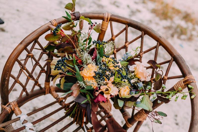 Ramo hermoso de la boda que consiste en diversas flores que mienten en una silla marrón vieja Manojo de flores imagenes de archivo