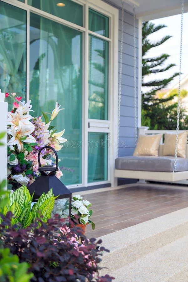 Ramo hermoso de la flor en un pote y una lámpara con la planta en un patio fotos de archivo