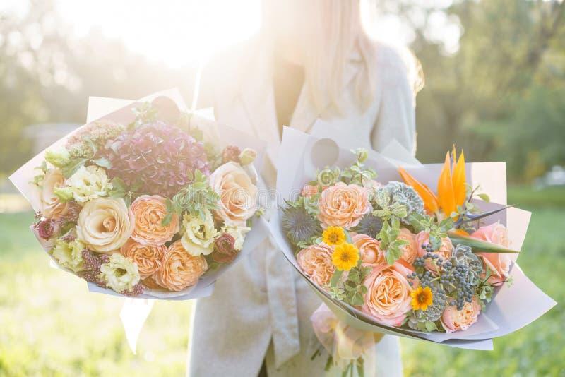 Ramo hermoso de la primavera dos Chica joven celebrando centros de flores con la variedad de colores Violeta, azul y melocotón fotografía de archivo libre de regalías