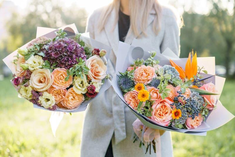 Ramo hermoso de la primavera dos Chica joven celebrando centros de flores con la variedad de colores Violeta, azul y melocotón imágenes de archivo libres de regalías