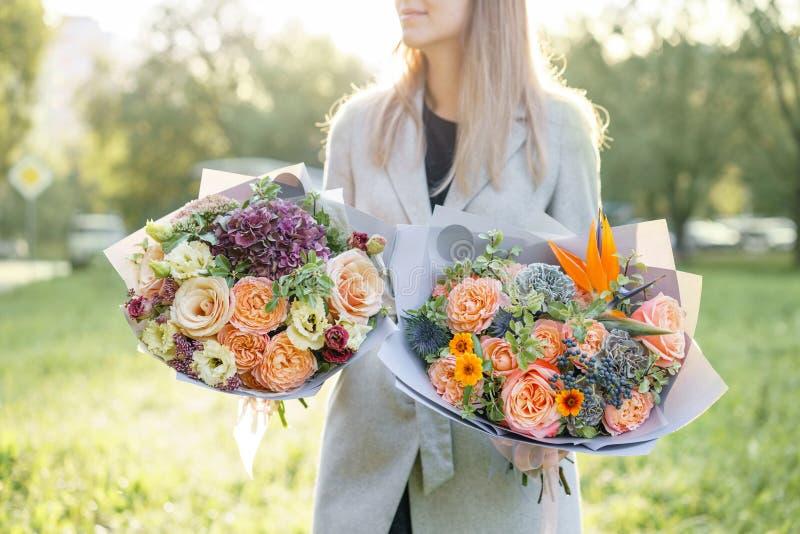 Ramo hermoso de la primavera dos Chica joven celebrando centros de flores con la variedad de colores Violeta, azul y melocotón fotos de archivo