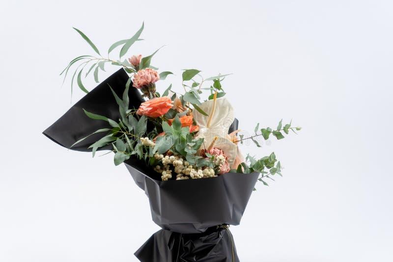 Ramo hermoso de las flores en papel negro del compañero Rosas y clavel rosado Fondo blanco fotos de archivo