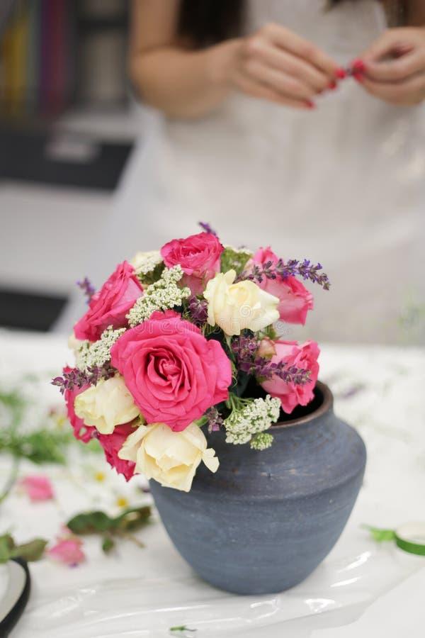 Ramo hermoso de las flores frescas en un florero en una tabla contra la perspectiva de la muchacha con la manicura roja fotografía de archivo libre de regalías