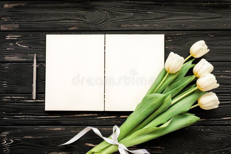 Ramo hermoso de los tulipanes blancos y del cuaderno abierto, pluma de plata en el fondo de madera negro imagenes de archivo