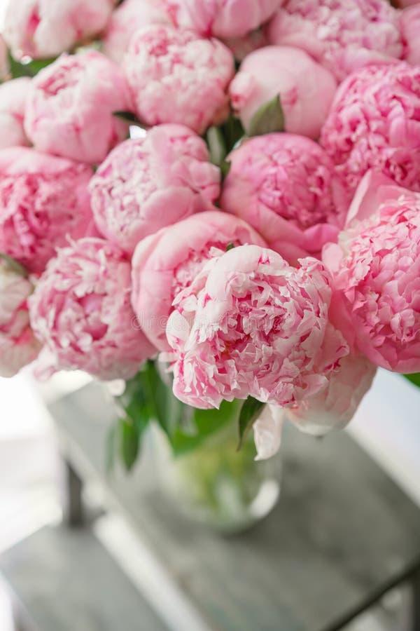 Ramo hermoso de peonías rosadas Composición floral, luz del día wallpaper Flores preciosas en el florero de cristal foto de archivo