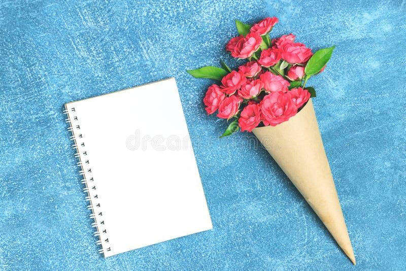 Ramo hermoso de pequeñas rosas rojas en documento del vintage sobre la tabla imagen de archivo