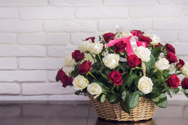 Ramo hermoso de rosas y de una cesta de madera foto de archivo
