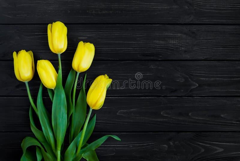 Ramo hermoso de tulipanes amarillos adentro en la tabla Visión superior, endecha plana imágenes de archivo libres de regalías