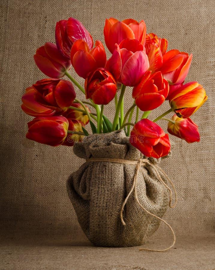 Ramo hermoso de tulipanes rojos brillantes en un florero fotos de archivo