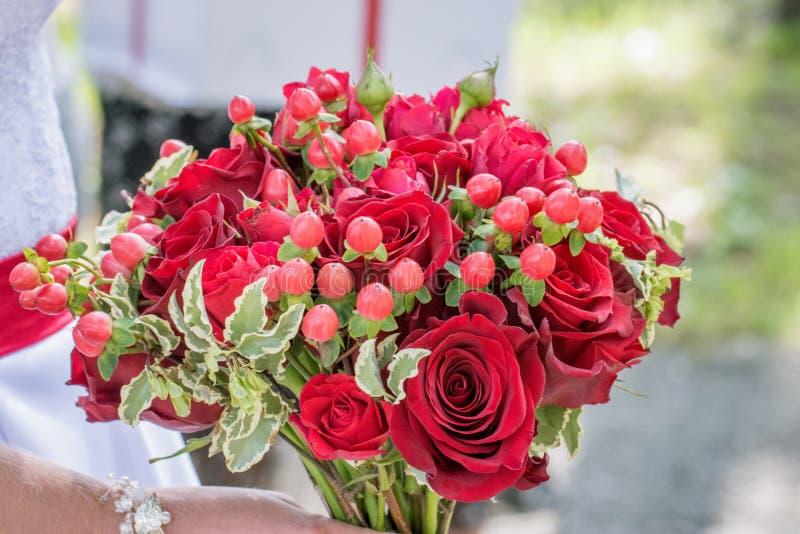 Ramo hermoso de una novia con el primer de las rosas rojas en un paseo o imagen de archivo libre de regalías