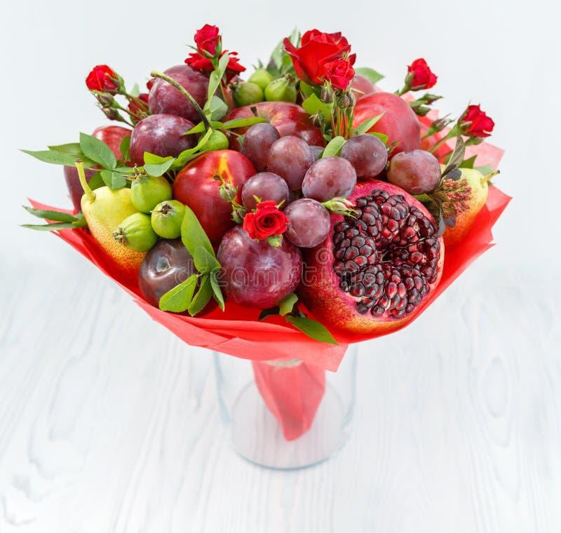 Ramo hermoso que consiste en la granada, manzanas, ciruelos y las rosas del escarlata que se colocan en un florero en una tabla d foto de archivo