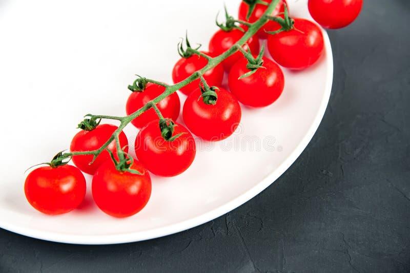 Ramo lungo dei pomodori ciliegia freschi maturi organici su un piatto bianco che mette sul fondo nero di struttura fotografia stock libera da diritti