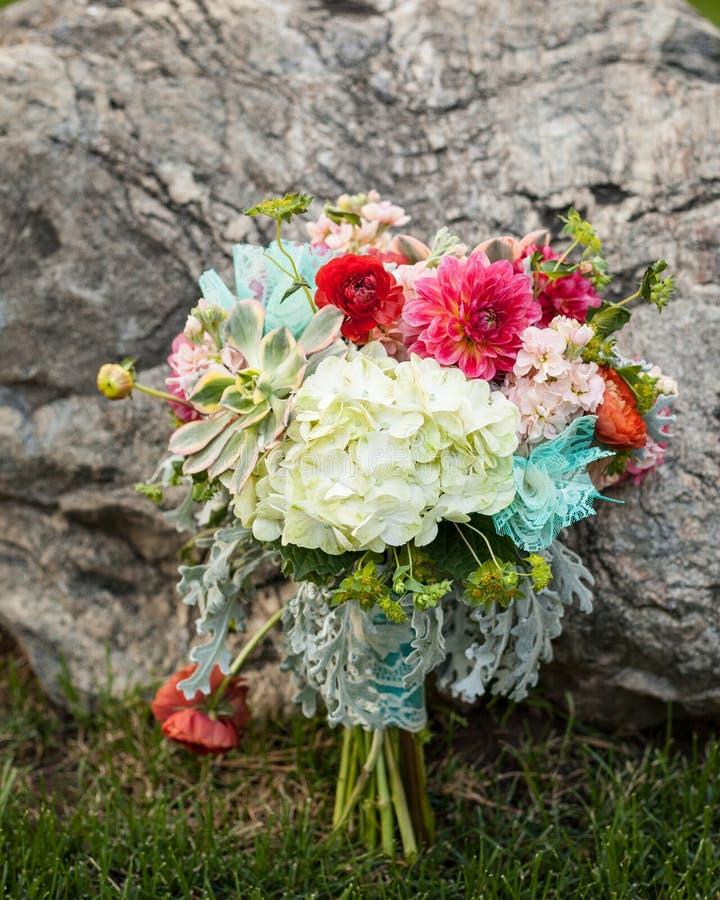 Ramo nupcial brillante y hermoso de flores que se sientan en la hierba y que se inclinan contra una roca fotos de archivo
