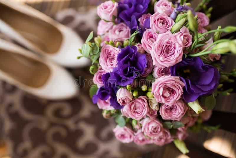 Ramo nupcial con las flores rosadas y púrpuras Preparación de la boda Accesorios de la boda Mañana del ` s de la novia fotografía de archivo