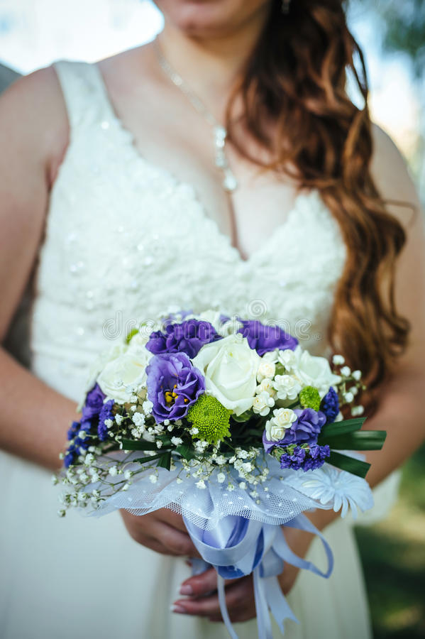 Ramo nupcial de flores en las manos de la novia imagenes de archivo