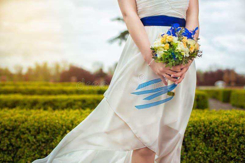 Ramo nupcial de flores en las manos de la novia fotografía de archivo libre de regalías