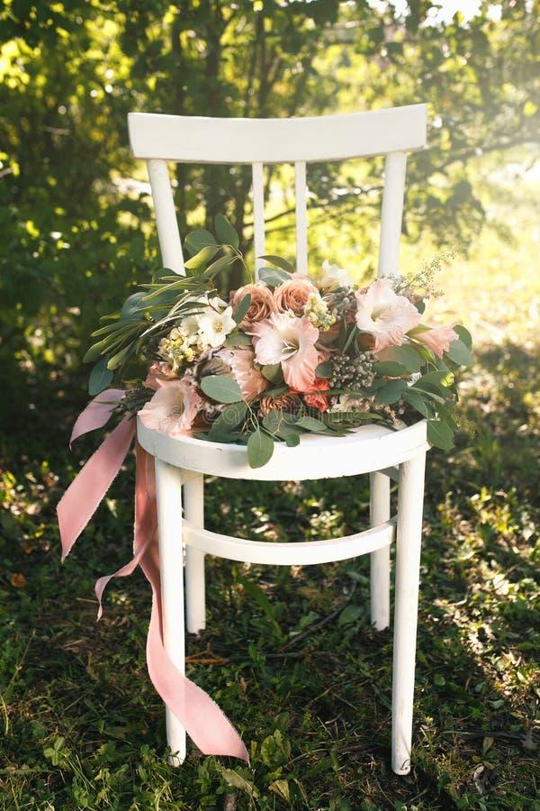 Ramo nupcial de las flores y del verdor rosados, mentiras en la silla de madera blanca del vintage fotos de archivo libres de regalías