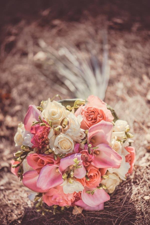 Ramo nupcial del otoño con las rosas rojas y blancas sobre hierba amarilla del otoño imagen de archivo libre de regalías