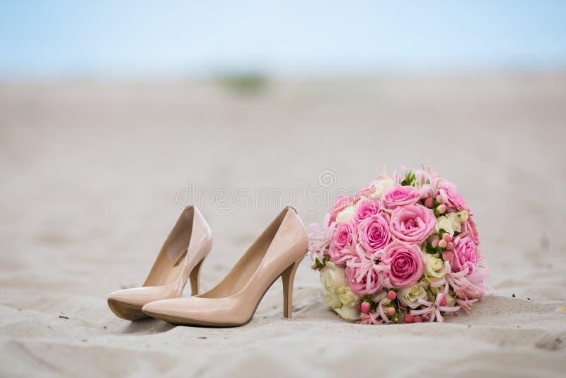 Ramo nupcial floral y zapatos de tacón alto beige laqueados contra la perspectiva de la arena y del mar fotos de archivo