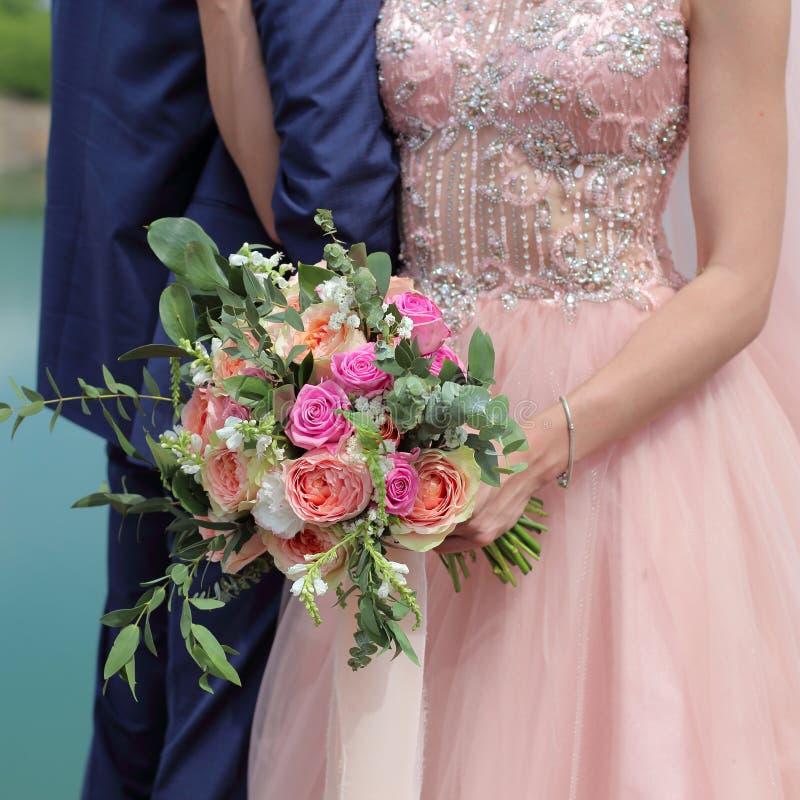 Ramo nupcial hermoso en las manos de la novia El ramo de la boda de rosas del melocotón de David Austin, rosa de la solo-cabeza s fotos de archivo