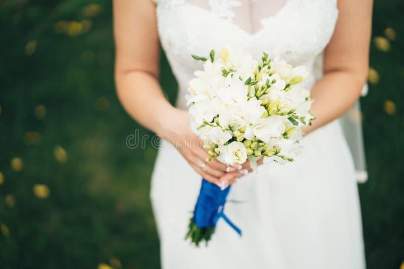Ramo nupcial precioso en manos del ` s de la novia Flores blancas de la primavera fotografía de archivo