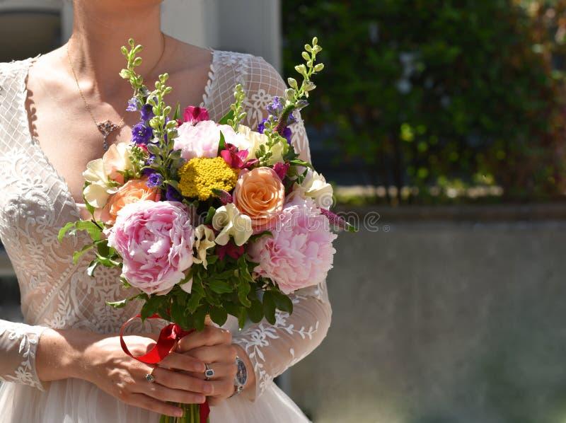 Ramo nupcial que es sostenido por una novia en una boda blanca en el Reino Unido imagenes de archivo