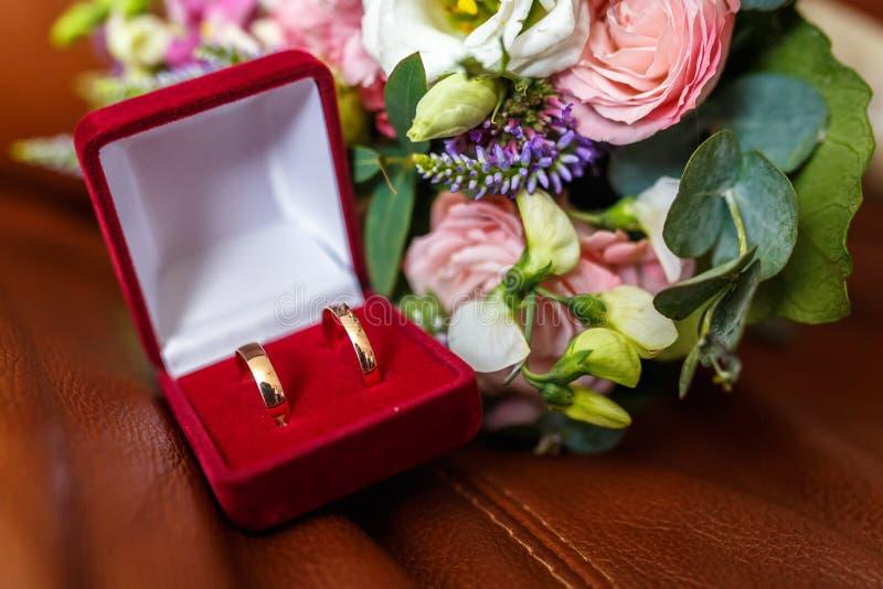 Ramo que se casa brillante de rosas y de orquídea rosadas blancas del verano con los wildflowers violetas con los anillos de boda imagenes de archivo
