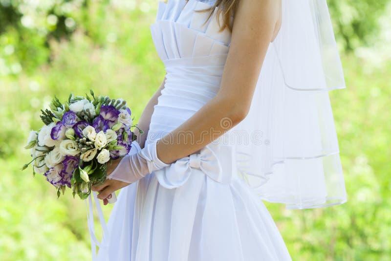 Ramo que se casa hermoso en las manos de la novia en el parque fotografía de archivo libre de regalías