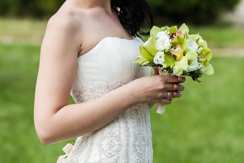 Ramo que se casa hermoso en las manos de la novia en parque foto de archivo