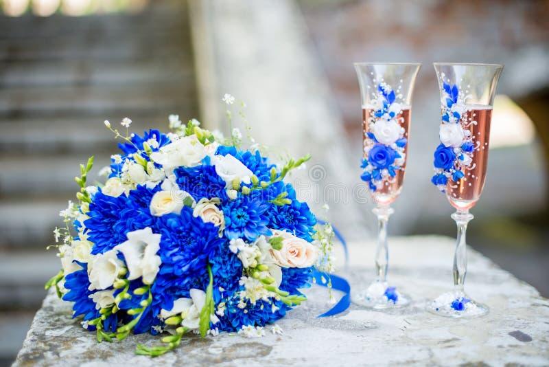 Ramo que se casa moderno hermoso de crisantemo azul, de fresia, de eustoma y de peonía Con casarse los vidrios del champán imagenes de archivo