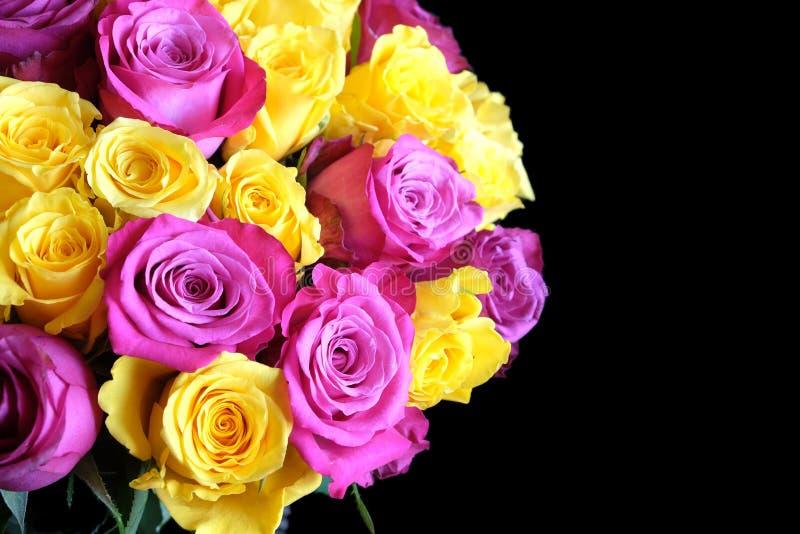 Ramo redondo hermoso de rosas del rosa y del uellow aisladas en la opinión superior del fondo negro fotografía de archivo