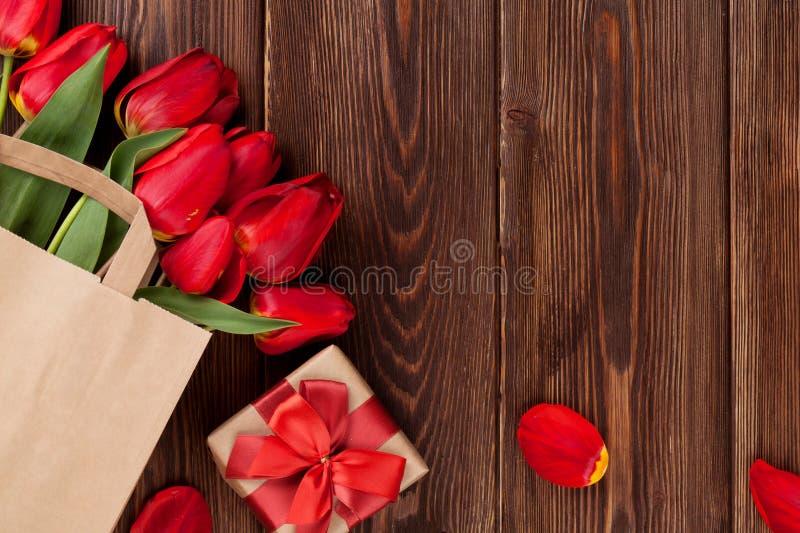 Ramo rojo de los tulipanes en bolso sobre la madera imagen de archivo