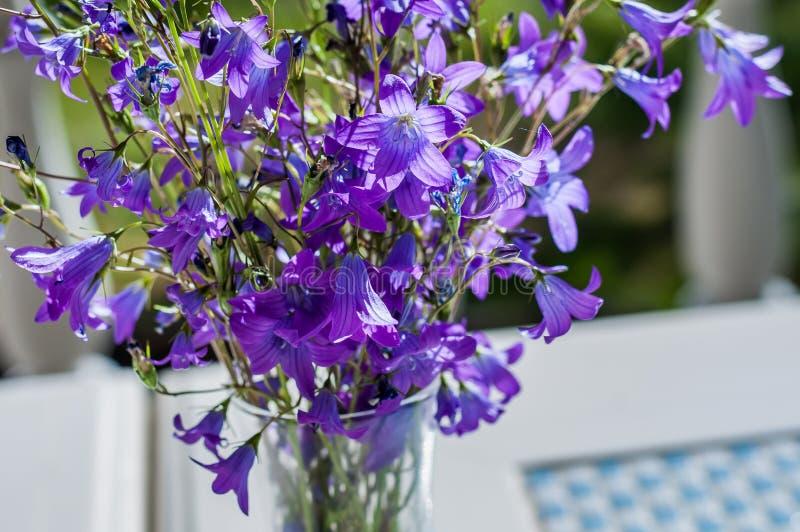 Ramo simple de flores salvajes en un florero de cristal, colocándose en la tabla para el humor romántico foto de archivo libre de regalías