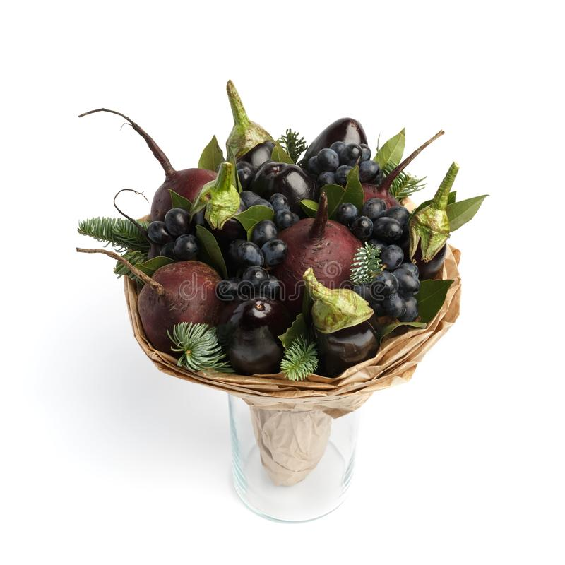 Ramo vegetal comestible original que consiste en las berenjenas, remolachas, uvas y hojas de la bahía, colocándose en un florero  imágenes de archivo libres de regalías