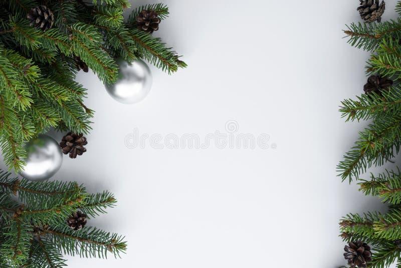Ramos de árvore do Natal, cones e quinquilharias de prata como um quadro com espaço da cópia para o texto no fundo branco Os feri fotos de stock