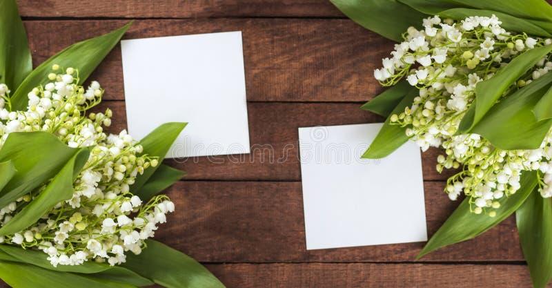 Ramos de lirios del valle con el espacio para el texto de las hojas de papel blancas en un fondo de madera foto de archivo