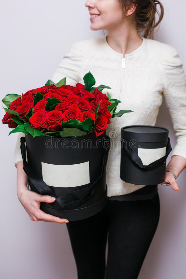 Ramos de lujo de flores en la caja del sombrero rosas en las mujeres de las manos Color rojo y negro imagen de archivo libre de regalías