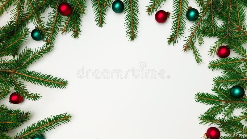 Ramos de uma beira da árvore de Natal em um lado em três lados com as bolas vermelhas e verdes em um fundo branco fotos de stock royalty free
