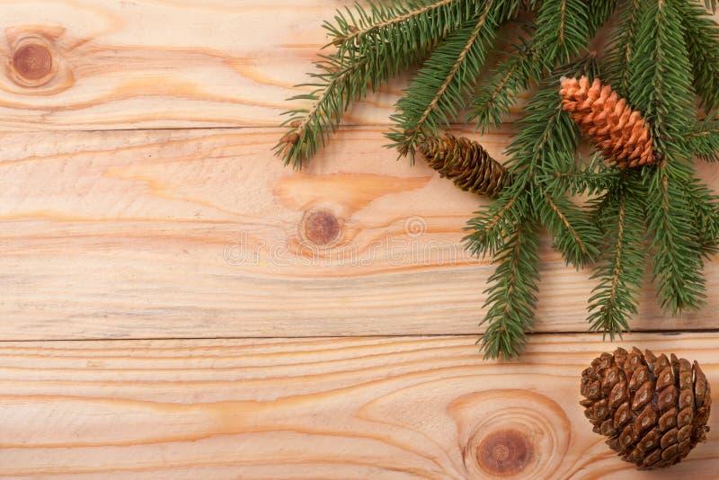 Ramos do abeto com cones em um fundo de madeira claro para o cartão de Natal fotografia de stock royalty free