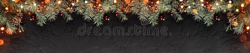 Ramos do abeto do Natal com os cones do pinho no fundo escuro do feriado com luz Tema do Xmas e do ano novo feliz Configuração li fotos de stock royalty free