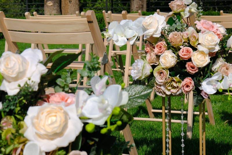 Ramos florales y sillas vacías de madera blancas en hierba verde Decoraciones de la ceremonia de boda imagen de archivo libre de regalías