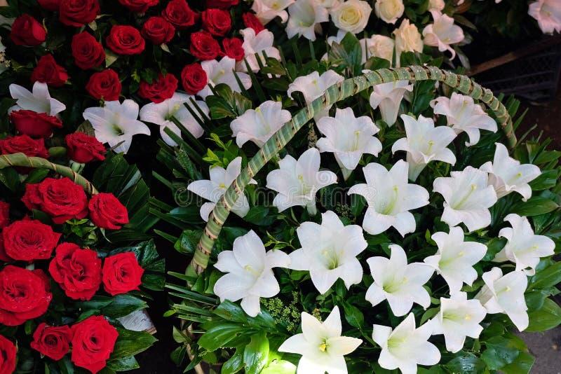 Ramos grandes de rosas rojas y de cestas grandes con los lirios blancos fotografía de archivo