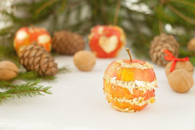 Ramos verdes e luzes douradas do Natal e maçã bonita no fundo branco, ano novo feliz foto de stock royalty free