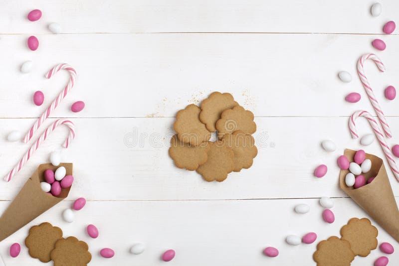 Ramowi kolorowi cukierki, pasiaści lizaki i ciastka, Odgórny widok, biały drewniany tło, kopii przestrzeń czerwona róża zdjęcia stock