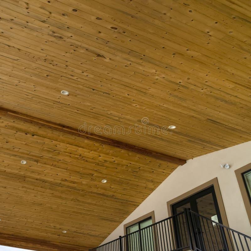Ramowy spód dach z brąz drewnianymi deskami i round podsufitowymi światłami przeciw niebu zdjęcie stock