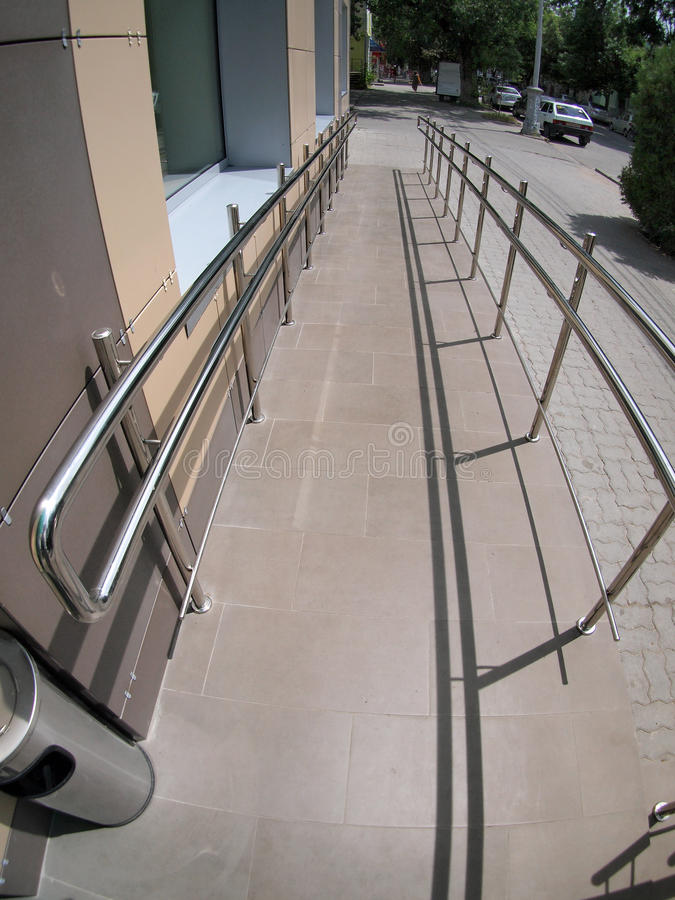 Ramp for physically challenged from the tiled pavement. With wide angle fisheye lens and distortion view stock image