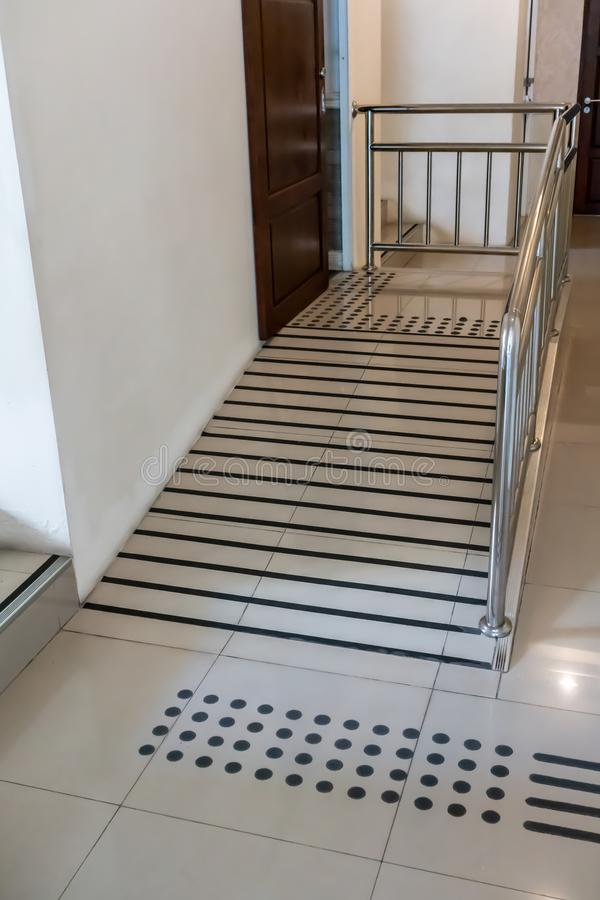 Ramp way with stainless steel handrail for support wheelchair disabled people infront of the disable toilet stock photo