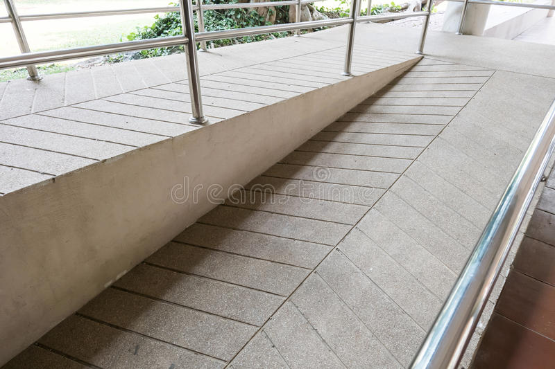 Ramp way for support wheelchair disabled people made from sand. And small gravel stone washed floor stock image